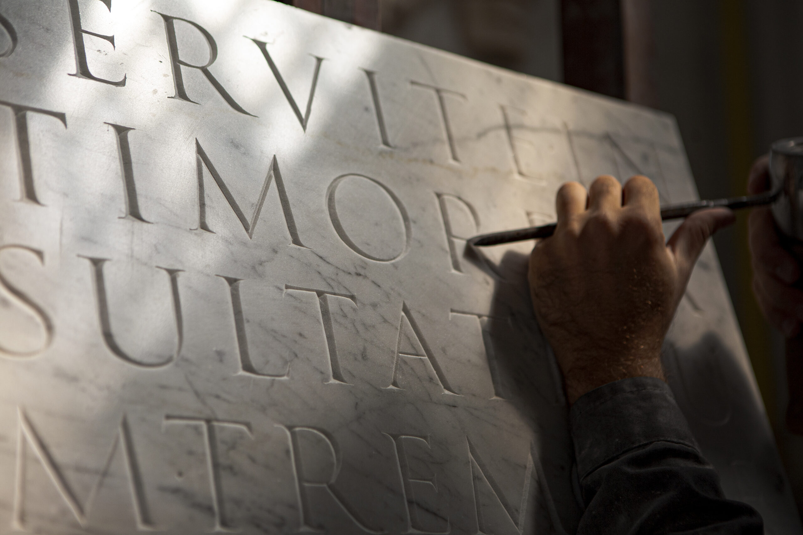 Close up of a letter carver's hand holding a chisel while carving Trajan letters on a marble plate